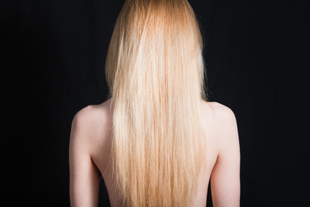 Back view of young girl with beautiful long blonde hair isolated on black Stock Photo