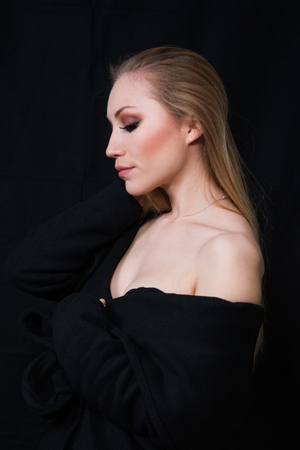Profile of sexy lady with glamour makeup and long blonde hair in long coat posing in studio, dark background. Elegant woman. Erotic noir concept.