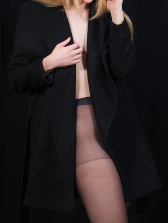Detail of sexy lady in long coat posing in studio, dark background. Elegant woman. Erotic noir concept.