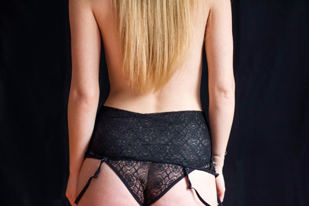 Back view of young sexy girl in black lace panties with isolated on black. Elegant woman wearing sensual lingerie. Erotic noir concept. Body detail.