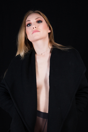 Sexy lady with glamour makeup and long blonde hair in nylons and long coat undressing, in studio. Elegant woman wearing black sensual lingerie. Erotic noir concept.