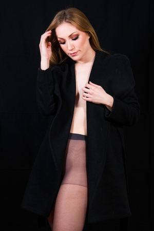 Sexy lady with in nylons and long coat undressing, dark background. Elegant woman wearing black sensual lingerie. Erotic noir concept.