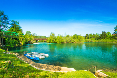 River shore with boats on Mreznica river in Belavici, Croatia