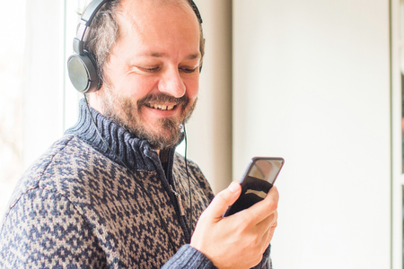 Smiling middle age man listening to music with headphones while standing next to window at home and holding smart phone Banco de Imagens