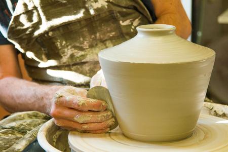 Artist potter in the workshop sculpting ceramic vase. Hands closeup. Small artistic craftsmen business concept.