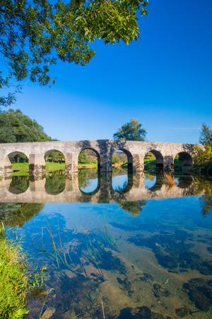 Croatia, Dobra river, old stone bridge in Novigrad, Karlovac county, beautiful countryside landscape and green nature