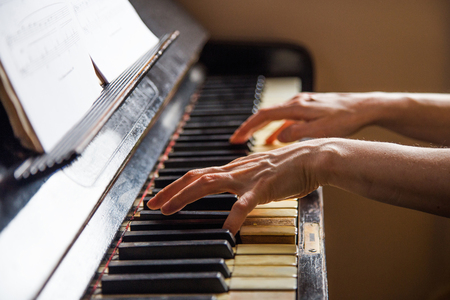 Close up fingers of woman pianist at the rusty piano keys, arms plays solo of music. Hands of female musician playing. Music instrument, solo pianist, song composer, hobby, practice study.