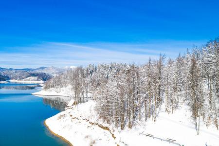Beautiful winter panoramic landscape in mountains, Lokvarsko lake in Croatia, woods under snow in Gorski kotar and Risnjak mountain in background from drone 免版税图像