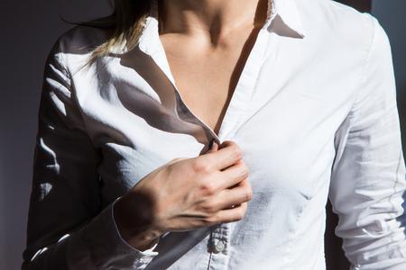 Mujer irreconocible desabrocharse la blusa blanca, junto a la ventana en la mañana sin rostro, pecho y hombros Foto de archivo