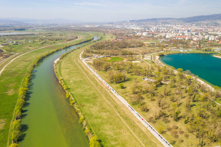 Zagreb, Croatia, Jarun lake, beautiful green recreation park area, sunny spring day, panoramic view from drone, city in background