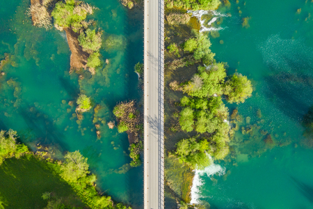 Croatia, road bridge over Mreznica river in Belavici village from drone, overhead shot countryside landscape view of waterfalls and trees in spring Stock Photo