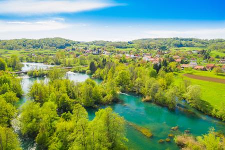 Croacia, campo verde, río Mreznica desde el aire, vista panorámica de la aldea de Belavici, cascadas en primavera, popular destino turístico complejo turístico