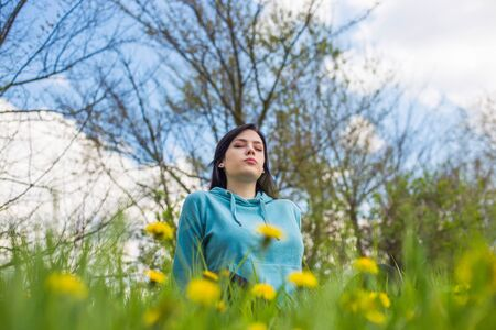 Girl in hoodie sitting on green meadow among flowers and meditating in nature background. Woman practicing meditation. Eyes closed.