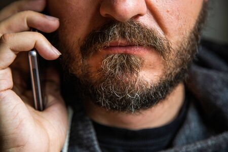 Close up portrait of bearded man talking on smart phone, focus on lips, no eyes, secret talk, criminal threatening someone Imagens