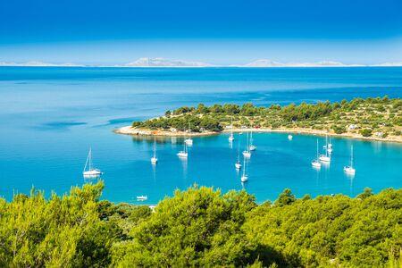 Panoramablick auf die Strandbucht von Kosirina auf der Insel Murter in Kroatien, verankerte Segelboote und Yachten auf blauem Meer