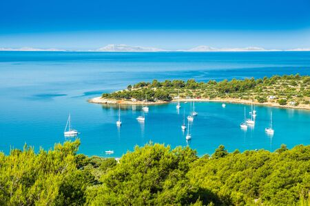 Panoramic view on Kosirina beach bay on Murter island in Croatia, anchored sailing boats and yachts on blue sea