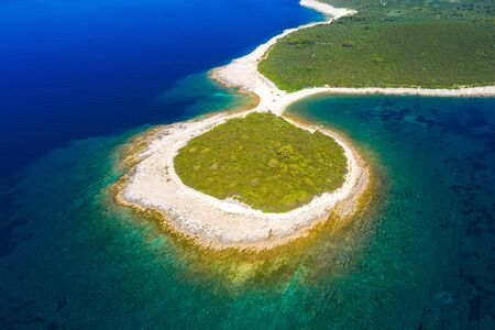 Rocky fish shaped cape in turquoise sea, clear blue water on the island of Dugi Otok in Croatia