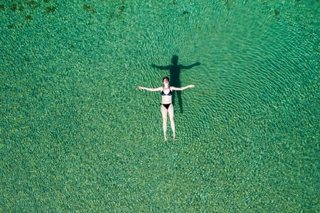 Woman in bikini floating on back on the surface of crystal clear water, young woman carefree on the sea, relaxing, Dugi otok island, Croatia, overhead drone view