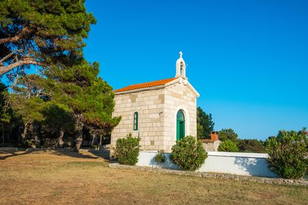 Croatia, island of Dugi Otok, beautiful old stone church of Veli Rat on the stone shore among the pines on sunny day, Mediterranean landscape Reklamní fotografie