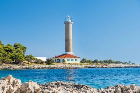 Croatia, island of Dugi Otok, old lighthouse of Veli Rat on the stone shore, beautiful seascape in foreground