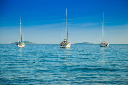 Yachting paradise, anchored sailing boats and yachts in the morning in blue bay on Croatian Adriatic, Kosirina bay on Murter island
