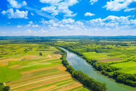 Wiejski krajobraz wsi w Chorwacji, rzeka Kupa wijąca się między polami rolnictwa, strzał z drone