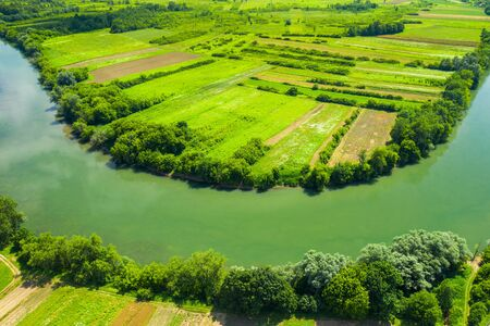 Rural countryside landscape in Croatia, Kupa river meandering between agriculture fields, shot from drone