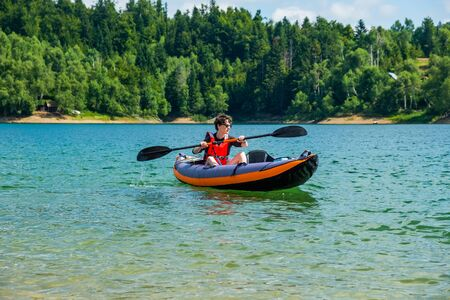 Young active woman kayaking in inflatable kayak on lake Lokve, in Gorski kotar, Croatia. Adventurous experience on a beautiful sunny day. Reklamní fotografie