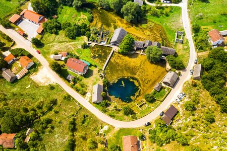 Croatia, region of Lika, Majerovo vrilo river source of Gacka and old wooden mills and cottages aerial drone view