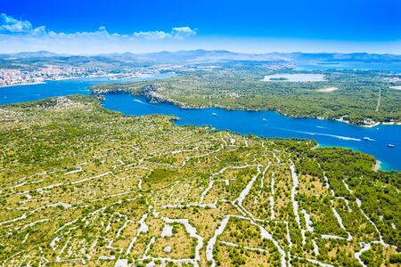 Croatian Adriatic coast, beautiful landscape in Sibenik channel, old agriculture fields and turquoise bay with yachts and boats, aerial view