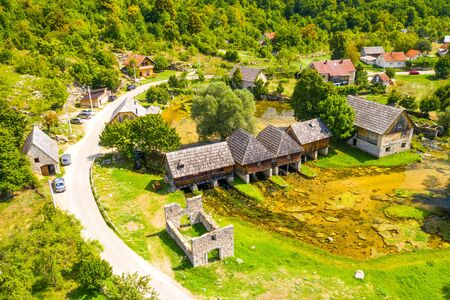 Croatia, countryside region of Lika, Majerovo vrilo river source of Gacka and old wooden mills and cottages aerial drone view