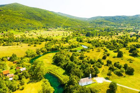 Croatia, countryside landscape, small stone church by Gacka river in region of Lika, aerial view