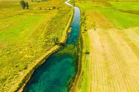 Beautiful Gacka river flowing, field aerial summer view, Lika region of Croatia