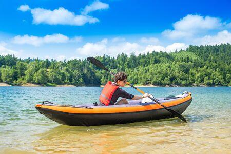 Woman paddling in inflatable kayak on lake Lokve, in Gorski kotar, Croatia. Adventurous experience in wild nature. Reklamní fotografie