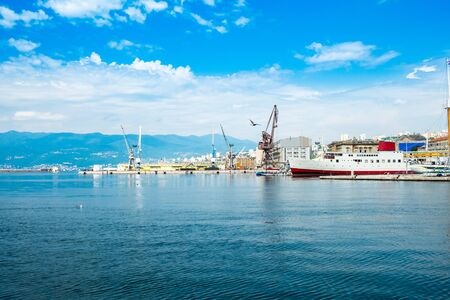 Croatia, city of Rijeka, ciew of harbor, seascape and skyline of the city center and old port cranes, blue sky with clouds