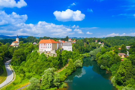 Panoramic view of the river Kupa and beautiful old Ozalj Castle on the hill in town of Ozalj, Croatia, drone aerial