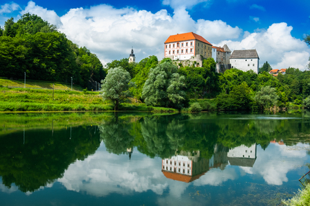 River Kupa and beautiful old Ozalj Castle on the hill in town of Ozalj, Croatia, reflection in water surface Redakční