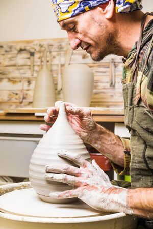 Profile portrait of potter artist making clay bowl or vase ceramics on the potter's wheel. Creating pottery art and handicraft modeling creation. Stock Photo