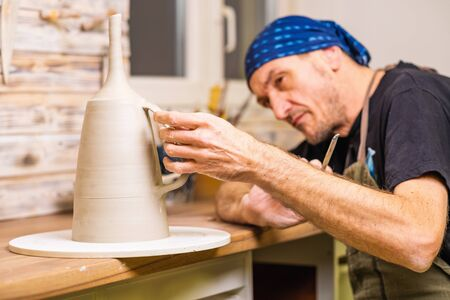Potter artist finishing works on newly hand made cup, small art business concept, shallow debt of field