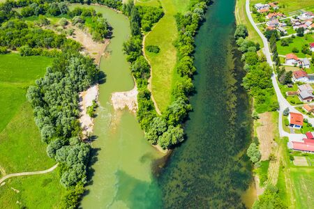 Rural countryside landscape in Croatia, confluence of Korana and Kupa rivers between agriculture fields and villages, panoramic view from drone