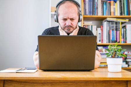 Man working from home office, worried face expression. Adult bearded man with headphones looking worried, sitting behind vintage desk at home, working remote Stock Photo