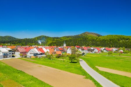 Croatia, town of Delnice, Gorski kotar, panoramic view of town center from drone in spring, mountain landscape in background