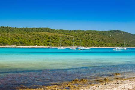 Azure turquoise lagoon on Sakarun beach on Dugi Otok island, Croatia, yachts anchored in clear sea water.