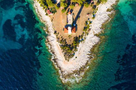Lighthouse of Veli Rat on the island of Dugi Otok, Croatia, beautiful seascape and rocks, overhead view from drone