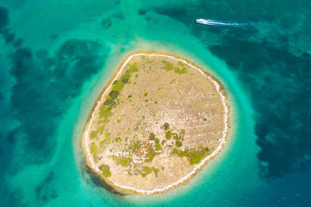 Adriatic sea Croatia, beautiful small island of Ricul in turquoise sea in Murter archipelago, aerial view of from drone, beat passing by