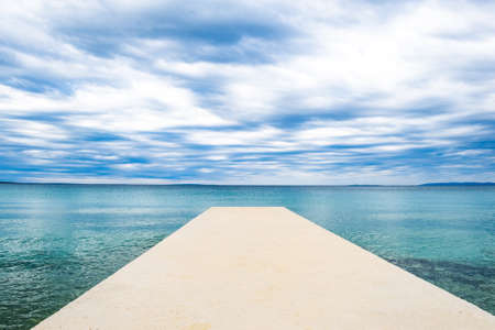 Croatia, island of Pag, turquoise water of Adriatic Sea and long pier on cloudy day Stock fotó