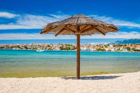 Adriatic sea shore in Croatia on Pag island, parasol on beautiful sand beach in town of Novalja
