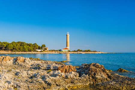 Lighthouse of Veli Rat on the island of Dugi Otok, Croatia, beautiful Adriatic seascape and rocks in foreground