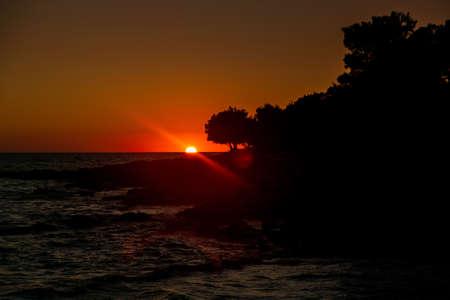 Beautiful sunset on Adriatic Sea in Croatia, waves on rocks on shore of Dugi Otok island. Amazing sea sunset and red sky on horizon. Stock fotó