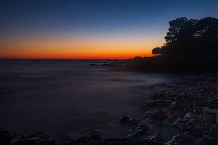 Beautiful evening on Adriatic Sea in Croatia, waves on rocks on shore of Dugi Otok island. Amazing sea sunset and red sky on horizon. Long exposure.